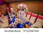 Small photo of Table setting at wedding reception. Served table with dishes, decorated by flower bouquets and chairs in white cloth. Utensil, cutlery and dish-ware on tablecloth