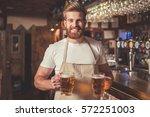 handsome bearded bartender in... | Shutterstock . vector #572251003