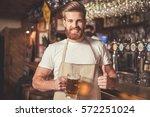 handsome bearded bartender in... | Shutterstock . vector #572251024