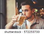 handsome guy is drinking beer... | Shutterstock . vector #572253733