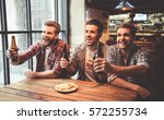 handsome friends are drinking... | Shutterstock . vector #572255734