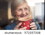 senior woman at the window... | Shutterstock . vector #572357338