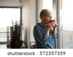 senior woman at the window... | Shutterstock . vector #572357359