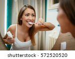 Beautiful Young Woman Brushing...