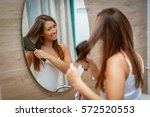 beautiful young woman combing... | Shutterstock . vector #572520553