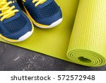 yoga mat and sport shoes on... | Shutterstock . vector #572572948