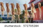 squid drying on a line in the... | Shutterstock . vector #572705284