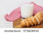 baguette slices with glass milk | Shutterstock . vector #572828920