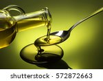 oil poured in a spoon... | Shutterstock . vector #572872663