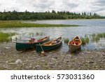 Three Canoes On A Lake's Rocky...
