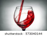 red wine pouring splash into... | Shutterstock . vector #573040144