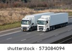 two white lorries driving side... | Shutterstock . vector #573084094