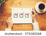 checklist with a person holding ... | Shutterstock . vector #573183268