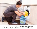 young husband man doing laundry ... | Shutterstock . vector #573203098