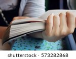 girl holding a book in her... | Shutterstock . vector #573282868
