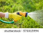 Hand With Garden Hose Watering...