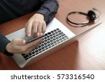 man hand using voip headset... | Shutterstock . vector #573316540