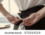 woman  tying up her apron... | Shutterstock . vector #573319219
