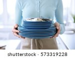 woman in apron holding dishes ... | Shutterstock . vector #573319228