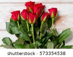 Stock photo a bouquet of roses on a wooden panel background 573354538