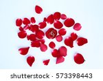 Stock photo abstract petals of red rose with wedding rings on white background 573398443