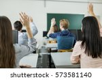 young students raising hands in ... | Shutterstock . vector #573581140