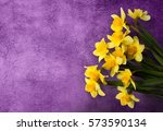 Small photo of Beautiful grunge Background with Yellow narcissus flowers on lilac texture. Colorful Greeting Card for Mothers Day, Birthday, March 8. Top view, Flat lay. Horizontal Image With Copy Space