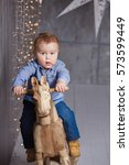 cute  boy on a wooden horse | Shutterstock . vector #573599449