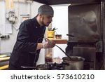 young male chef cooking in... | Shutterstock . vector #573610210
