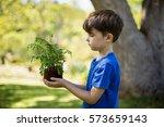 boy holding sapling plant in... | Shutterstock . vector #573659143
