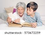 grandson is looking at photo... | Shutterstock . vector #573672259