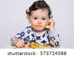Portrait Of A Cute Baby Eating...