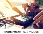 Small photo of Close up man calculate cost on desk at home.
