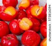 Small photo of Closeup of Malpighia glabra (red acerola), tropical fruit in bowl on gray background. Selective focus.