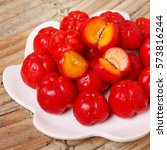 Small photo of Tropical fruit Malpighia glabra (red acerola) on plate on wooden table. Selective focus
