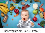 baby surrounded with fruits and ... | Shutterstock . vector #573819523