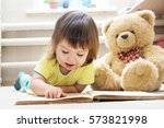 Little girl reading book lying...