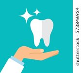 a healthy tooth on the hand of... | Shutterstock .eps vector #573846934