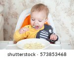 little baby boy eating sitting... | Shutterstock . vector #573853468