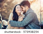 Small photo of Happy young couple hugging and laughing outdoors.