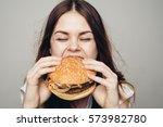 young woman eating hamburger...   Shutterstock . vector #573982780