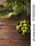 Small photo of Green olives in a ceramic bowl on a wooden background. Background of olives. Copyspace. Green olives and branch of bay leaf. Bay leaf. Copyspace