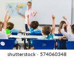 kids raising hand in classroom... | Shutterstock . vector #574060348