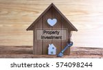 Small photo of Conceptual image of miniature home icon made from wood and word written PROPERTY INVESTMENT on wooden base.Selective focus.