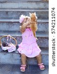 Stock photo very happy beautiful little girl in a pink dress and pink headband sitting on stairs holding red 574211074