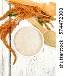 Small photo of Flour amaranth in a bowl, a spoon with grain, brown flower with green leaves on the background of the wooden planks on top