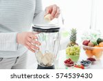 woman putting a banana in a... | Shutterstock . vector #574539430
