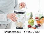 woman putting a banana in a... | Shutterstock . vector #574539430