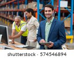 Small photo of Focus on manager is smiling and holding a tablet in front of his colleagues in a warehouse