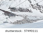 Chairlifts running above a mountain village - shot in Livigno, Italian Alps - stock photo